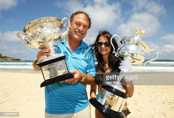 Former tennis player John Newcombe and Russian student Masha pose with the Norman Brookes Challenge Cup and the Daphne Akhurst Memorial Cup during...