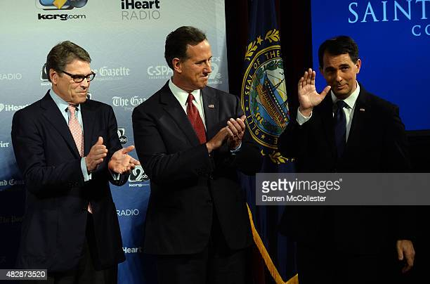 Former Texas Gov Rick Perry former US Sen Rick Santorum and Wisconsin Gov Scott Walker stand on the stage prior to the Voters First Presidential...
