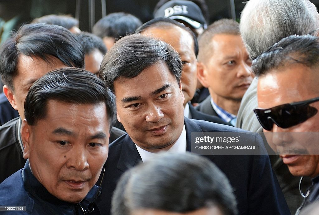 Former Thai prime minister Abhisit Vejjajiva (C) arrives at a justice ministry building to be charged with murder over a civilian's death during a crackdown on anti-government rallies two years ago, in Bangkok on December 13, 2012. Abhisit, along with his then-deputy Suthep Thaugsuban, were to be charged at the Department of Special Investigation (DSI), making them the first officials to face a court over Thailand's worst political violence in decades. AFP PHOTO/Christophe ARCHAMBAULT