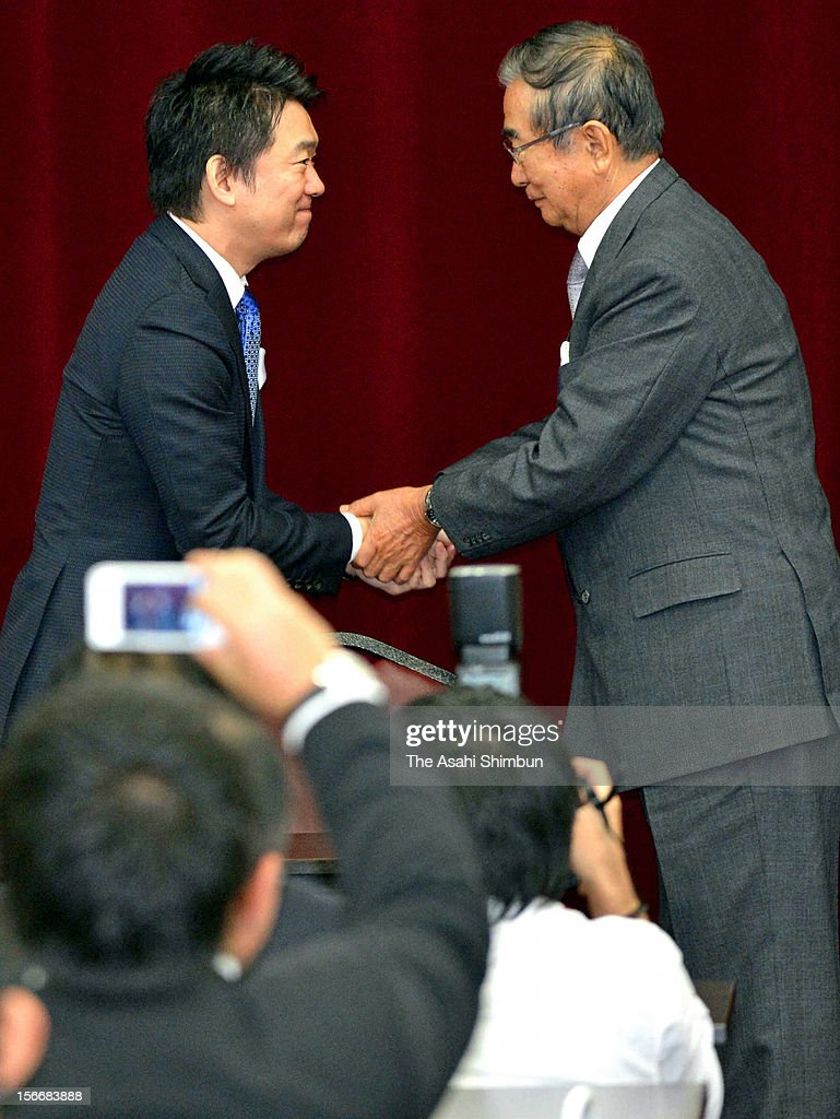 Former Tokyo governor Shintaro Ishihara and Osaka City mayor Toru Hashimoto shake hands at the Japan Restoration Party general meeting on November 17, 2012 in Osaka, Japan. Ishihara's Sunrise Party will be dissolved and merge to Hashimoto's Japan Restoration Party, Ishihara will be appointed as new president of the party and Hashimoto will be their acting president, and will seek more coalitions with small parties eyeing on December 16 general election.