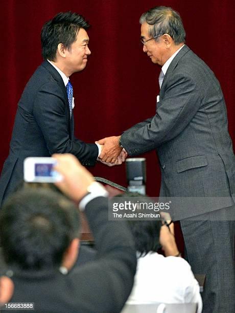 Former Tokyo governor Shintaro Ishihara and Osaka City mayor Toru Hashimoto shake hands at the Japan Restoration Party general meeting on November 17...