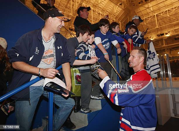 Former Toronto Maple Leaf Gary Roberts signs autographs prior to the 2013 Hockey Hall of Fame Legends Classic game at the Mattamy Athletic Center on...