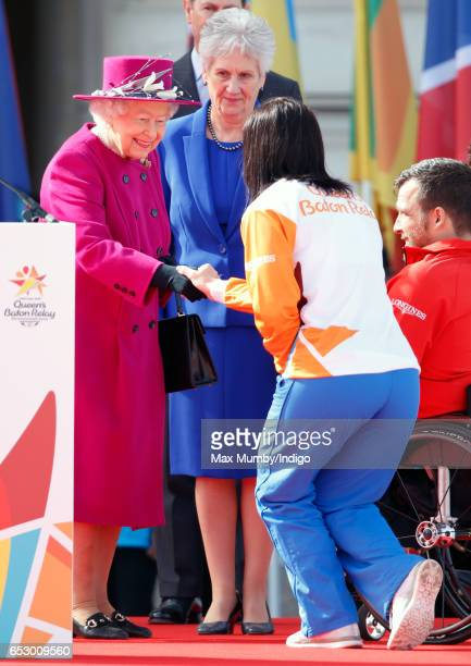 Former track cyclist Anna Meares of Australia curtsies to Queen Elizabeth II during the launch of The Queen's Baton Relay for the XXI Commonwealth...