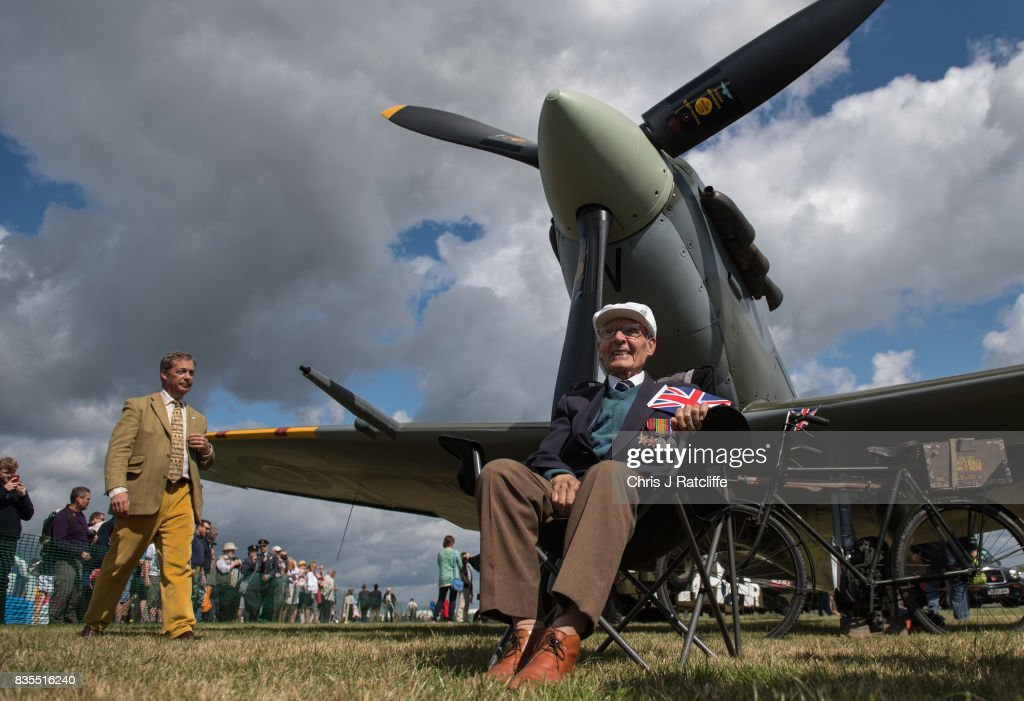 Former UKIP leader Nigel Farage walks past a Spitfire on display as a veteran sits underneath it at the Biggin Hill Festival of Flight on August 19, 2017 in Biggin Hill, England. The Biggin Hill Festival of Flight is an annual airshow event and in 2017 the airport is celebrating its centenary. The airport only became exclusively business and general aviation in 1959, prior to which it was used by the British Royal Air Force.