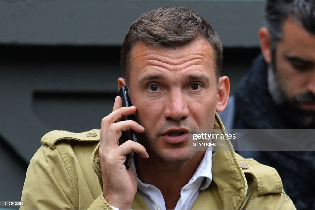 Former Ukrainian footballer Andriy Shevchenko (C) sits on centre court to watch Serbia's Novak Djokovic play against France's Adrian Mannarino during their men's singles second round match on the third day of the 2016 Wimbledon Championships at The All England Lawn Tennis Club in Wimbledon, southwest London, on June 29, 2016. / AFP / GLYN
