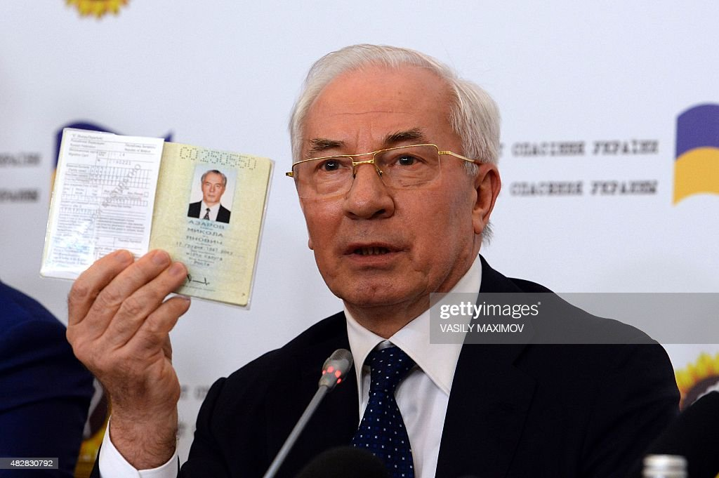 Former Ukrainian Prime Minister Nikolai Azarov holds up his Ukrainian passport during a press conference of the newly created 'Committee for the Salvation of Ukraine' in Moscow on August 3, 2015.