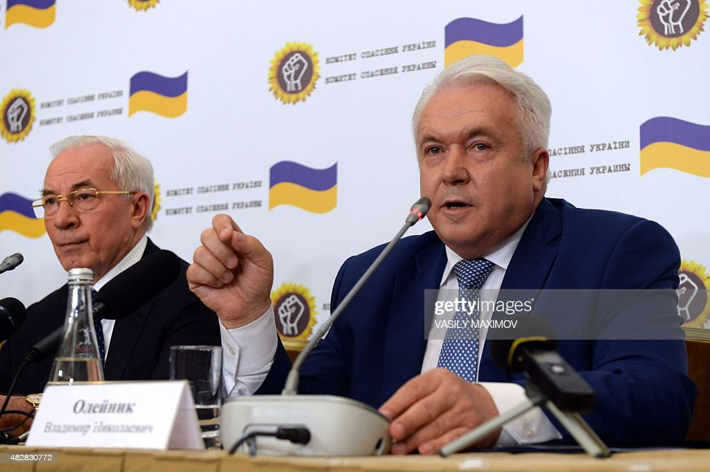 Former Ukrainian Prime Minister Nikolai Azarov (L) looks on as former deputy of the Ukrainian Parliament Verkhovna Rada Vladimir Oleynik (R) speaks during a press conference of the newly created 'Committee for the Salvation of Ukraine' in Moscow on August 3, 2015.