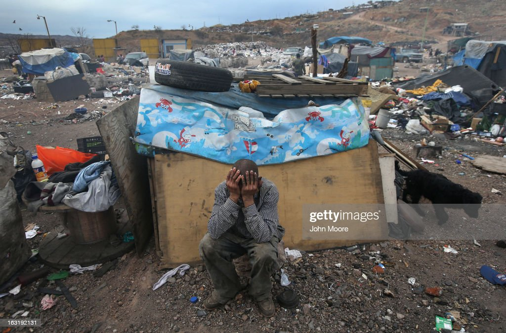 Former undocumented immigrant Arturo Santana sits in front of his modest home at the Tirabichi garbage dump on March 5, 2013 in Nogales, Mexico. He said he had been living and working in Des Moines, Iowa when he was picked up and deported by U.S. Customs and Border Protection agents in 2010. He said he still has 3 children living there with their mother. About 30 families live at the landfill, searching for recyclables to sell for a living. Many have received protective gloves from the nearby non-profit Home of Hope and Peace, which plans to expand its assistance to Tirabichi residents.