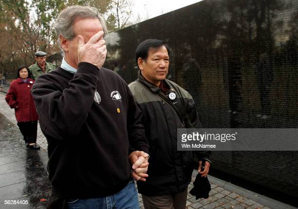 Former United States Marine Frank Corcoran wipes away tears as he tours the Vietnam War Memorial Wall with Ho Sy Hai a veteran of the North...