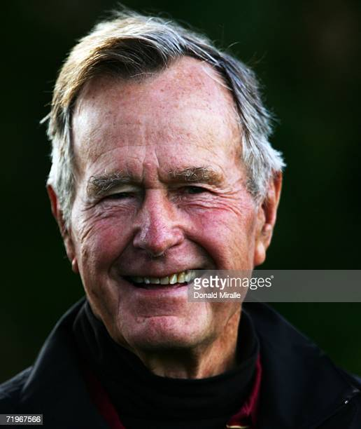 Former United States President George Bush smiles as he watches the action during the morning fourballs of the first day of the 2006 Ryder Cup at The...