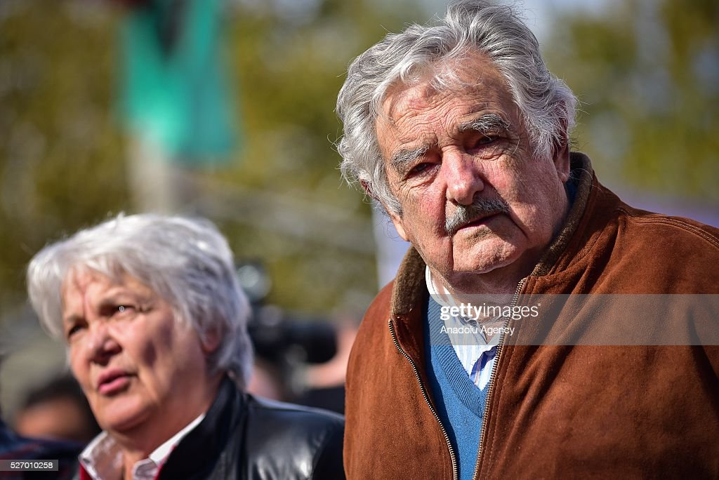 Former Uruguayan President Jose Mujica (R) and his wife Lucia Topolansky (L) take part in a rally to mark May Day, International Workers' Day in Montevideo on May 1, 2016.