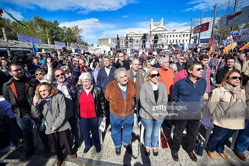 Former Uruguayan President Jose Mujica (R-4) and his wife Lucia Topolansky (R-5) take part in a rally to mark May Day, International Workers' Day in Montevideo on May 1, 2016.