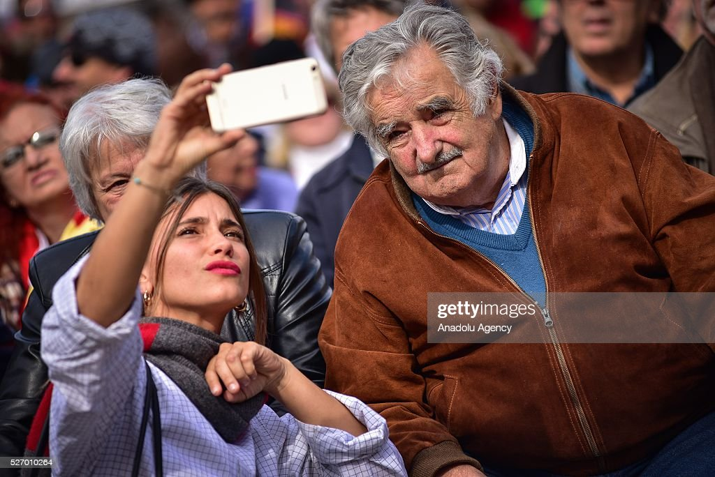 Former Uruguayan President Jose Mujica (R) poses for a selfie with a woman as he takes part in a rally to mark May Day, International Workers' Day in Montevideo on May 1, 2016.