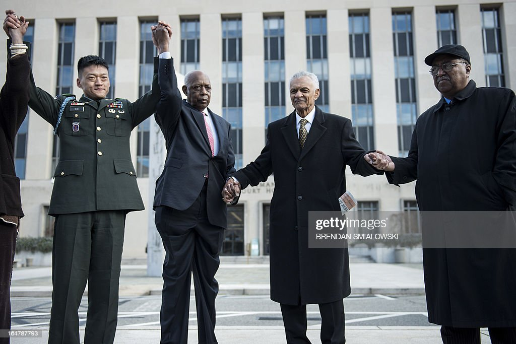 """Former US Army Lt. Dan Choi(L), a gay rights activist and opponent of 'Don't ask Don't Tell', stands with Joe Beasley (2L), of the Rainbow Push, American Civil Rights era icon Reverend C.T. Vivian (2R) and Dr. Charles Steele Jr. (R), Chief Executive Officer of the Southern Christian Leadership Conference at the E. Barrett Prettyman Federal Courthouse March 28, 2013 in Washington, DC. The trial of Choi, which began in August 2011, resumes Thursday in federal court. The former Iraq War vet and graduate of West Point is going to trial to face charges that stem from a November 2010 arrest for chaining himself to the White House fence to protest """"Don't Ask, Don't Tell."""" AFP PHOTO/Brendan SMIALOWSKI"""