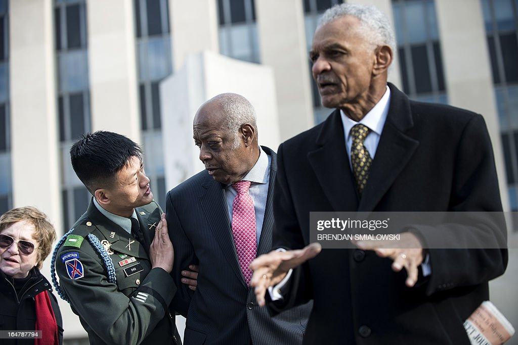 """Former US Army Lt. Dan Choi(L), a gay rights activist and opponent of 'Don't ask Don't Tell', talks with Joe Beasley (2R), of the Rainbow Push, as American Civil Rights era icon Reverend C.T. Vivian (R) speaks outside the E. Barrett Prettyman Federal Courthouse March 28, 2013 in Washington, DC. The trial of Choi, which began in August 2011, resumes Thursday in federal court. The former Iraq War vet and graduate of West Point is going to trial to face charges that stem from a November 2010 arrest for chaining himself to the White House fence to protest """"Don't Ask, Don't Tell."""" AFP PHOTO/Brendan SMIALOWSKI"""