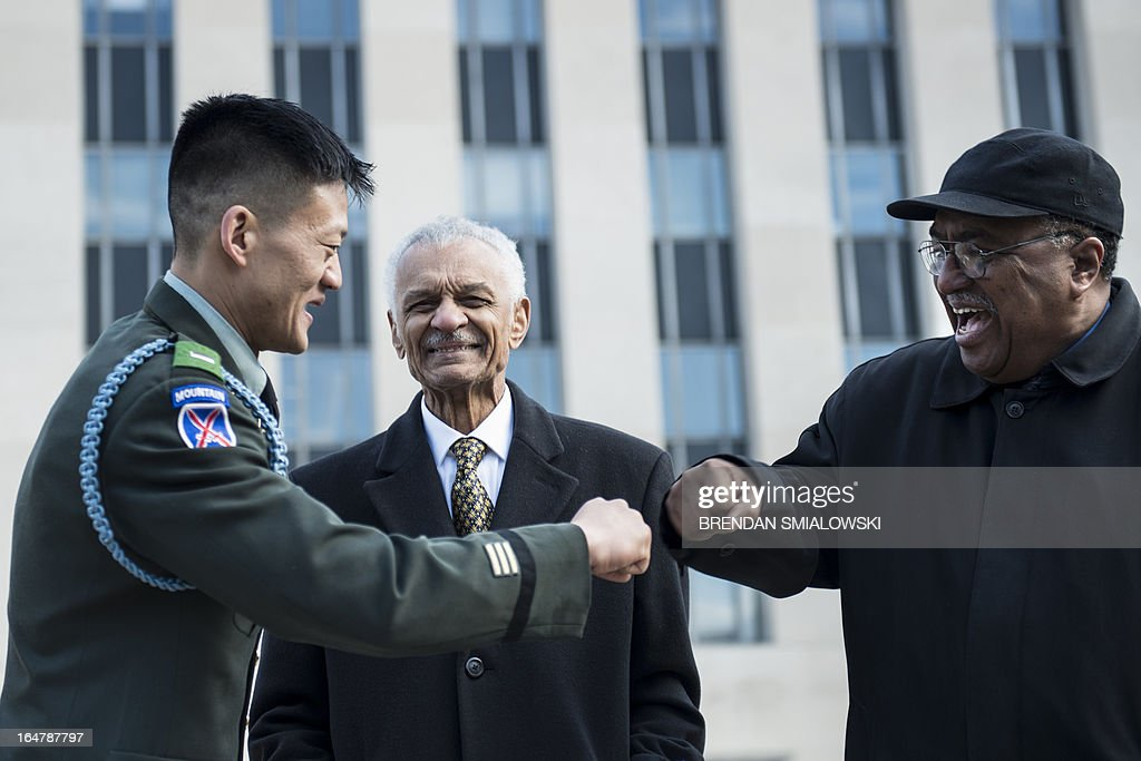 "Former US Army Lt. Dan Choi(L), a gay rights activist and opponent of 'Don't ask Don't Tell', fist bumps Dr. Charles Steele Jr. (R), Chief Executive Officer of the Southern Christian Leadership Conference, as American Civil Rights era icon Reverend C.T. Vivian as he arrives at the E. Barrett Prettyman Federal Courthouse March 28, 2013 in Washington, DC. The trial of Choi, which began in August 2011, resumes Thursday in federal court. The former Iraq War vet and graduate of West Point is going to trial to face charges that stem from a November 2010 arrest for chaining himself to the White House fence to protest ""Don't Ask, Don't Tell."" AFP PHOTO/Brendan SMIALOWSKI"