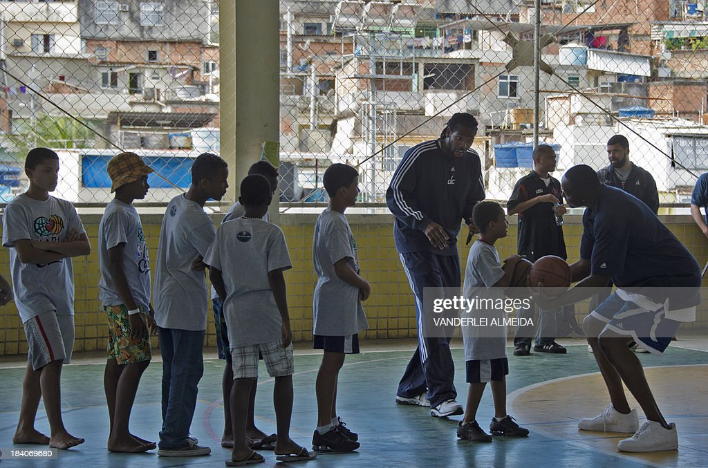 Former US basketball player and NBA ambassador Horace Grant (R), and Brazilian NBA's Washington Wizards player, Nene (3-R), teach children of the Alemao favela complex in Rio de Janeiro, Brazil on October 11, 2013, in an initiative supported by the Rio 2016 Organizing Commitee's Education Department. An exhibition match between the Chicago Bulls and the Washington Wizards will take place Saturday in Rio.