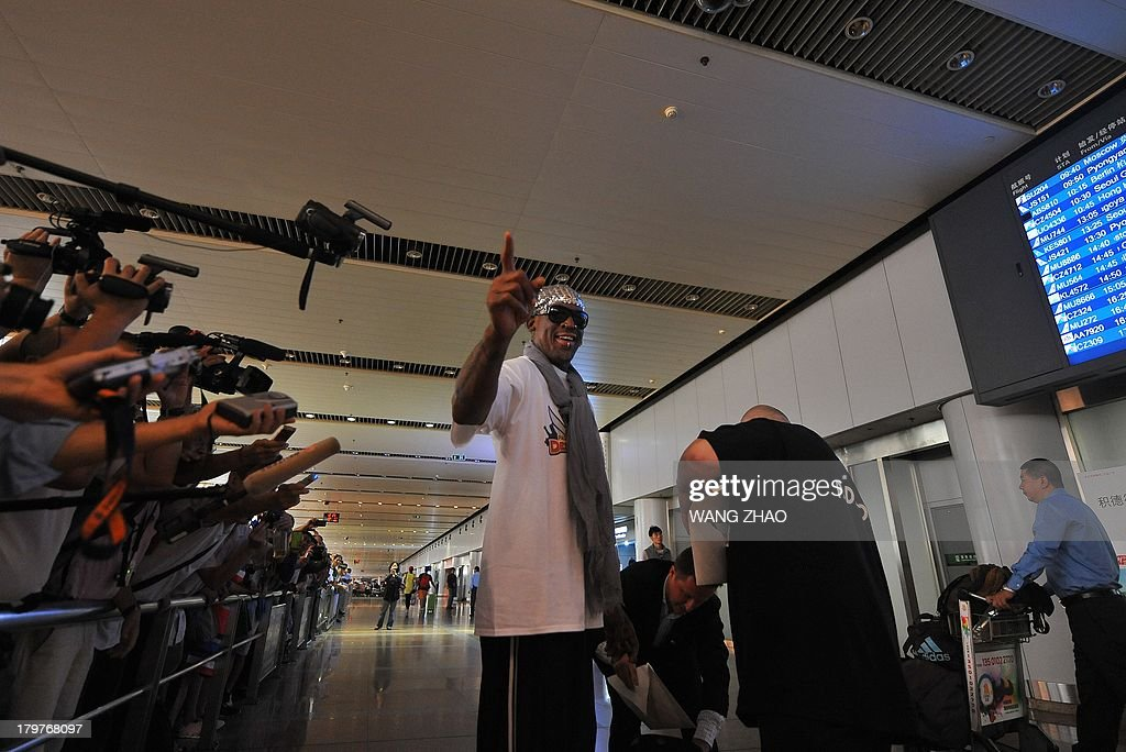 Former US basketball player Dennis Rodman gestures to members of the media as he arrives at Beijing International Airport from North Korea in Beijing on September 7, 2013. Rodman returned to China from Pyongyang on September 7 after a five-day trip when he met North Korean leader Kim Jong-Un, but without jailed American Kenneth Bae. AFP PHOTO / WANG ZHAO