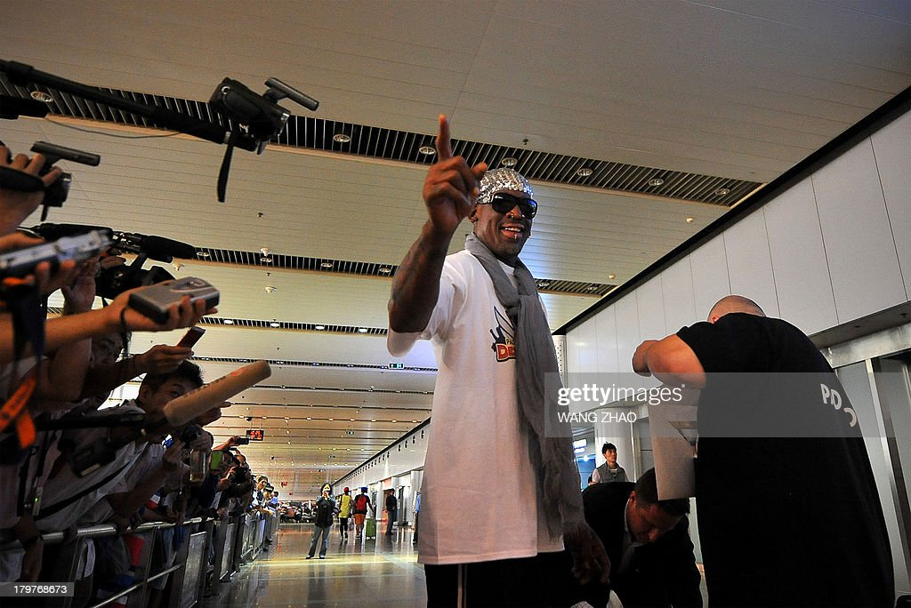 Former US basketball player Dennis Rodman gestures to the media as he arrives at Beijing International Airport from North Korea on September 7, 2013. Rodman returned to China from Pyongyang on September 7 after a five-day trip when he met Kim Jong-Un, but without jailed American Kenneth Bae. AFP PHOTO / WANG ZHAO