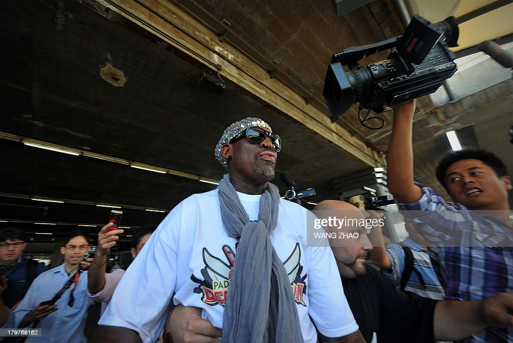 Former US basketball player Dennis Rodman is surrounded by members of the media as he arrives at Beijing International Airport from North Korea on September 7, 2013. Rodman returned to China from Pyongyang on September 7 after a five-day trip when he met North Korean leader Kim Jong-Un, but without jailed American Kenneth Bae. AFP PHOTO / WANG ZHAO