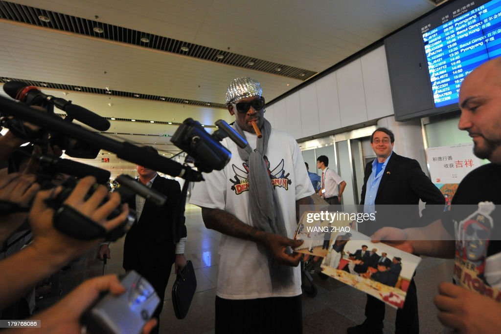 Former US basketball player Dennis Rodman (C) shows pictures from his trip to North Korea to members of the media as he arrives at Beijing International Airport on September 7, 2013. Rodman returned to China from Pyongyang on September 7 after a five-day trip when he met Kim Jong-Un, but without jailed American Kenneth Bae.