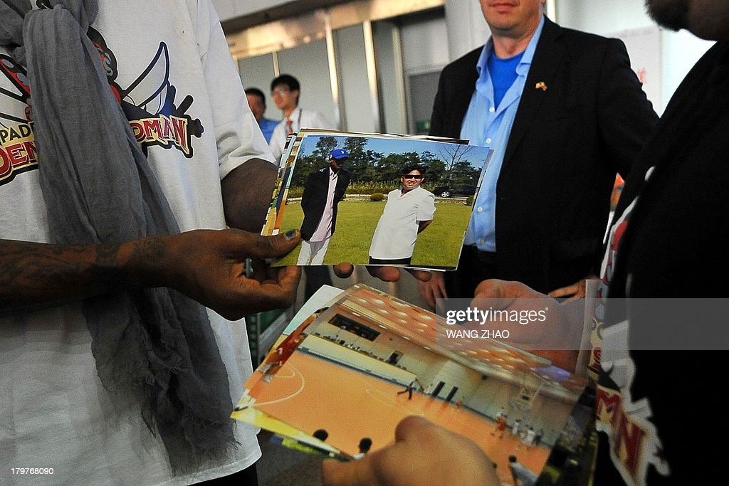 Former US basketball player Dennis Rodman shows pictures of him reportedly with North Korean leader Kim Jong-Un to media as he arrives at Beijing International Airport on September 7, 2013. Rodman returned to China from Pyongyang on September 7 after a five-day trip when he met Kim Jong-Un, but without jailed American Kenneth Bae. AFP PHOTO / WANG ZHAO