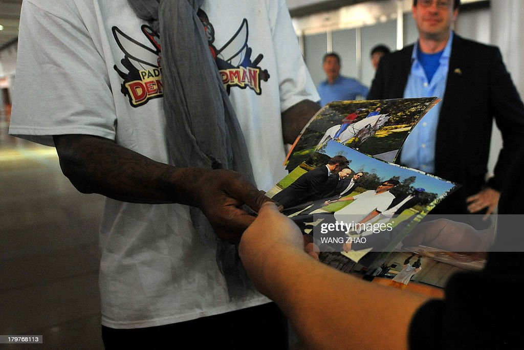 Former US basketball player Dennis Rodman (L) shows pictures of him reportedly with North Korean leader Kim Jong-Un to media as he arrives at Beijing International Airport on September 7, 2013. Rodman returned to China from Pyongyang on September 7 after a five-day trip when he met Kim Jong-Un, but without jailed American Kenneth Bae. AFP PHOTO / WANG ZHAO