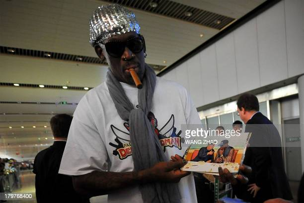 Former US basketball player Dennis Rodman shows pictures of him reportedly with North Korean leader Kim JongUn to media as he arrives at Beijing...