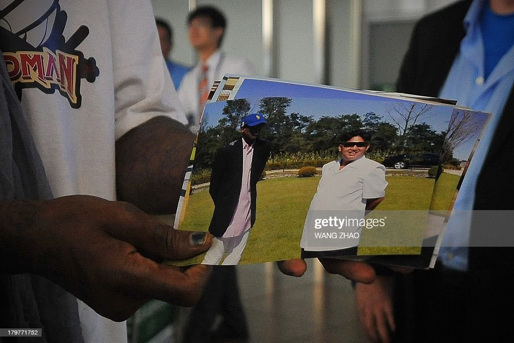 Former US basketball player Dennis Rodman (L) shows pictures of him reportedly with North Korean leader Kim Jong-Un to media as he arrives at Beijing International Airport on September 7, 2013. Rodman returned to China from Pyongyang on September 7 after a five-day trip when he met Kim Jong-Un, but without jailed American Kenneth Bae.