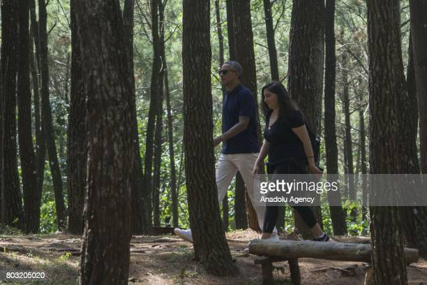 Former US President Barack Obama walks with a staff during his visit to Becici Pine Forest in Yogyakarta Indonesia on June 29 2017 Barack Obama and...