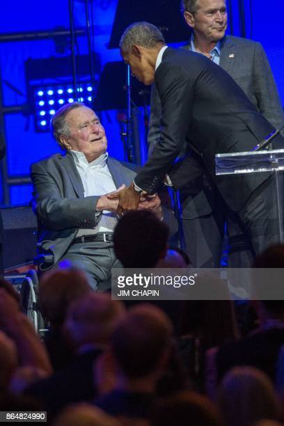 Former US President Barack Obama with President George W Bush greets President George H W Bush during the Hurricane Relief concert in College Station...