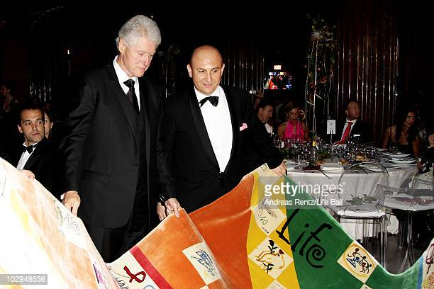 Former US President Bill Clinton and Ali Rahimi look at the Life Ball Carpet designed by Rahimi during the amfAR Gala Vienna 2010 as part of the Life...