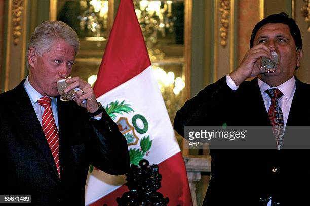 Former US President Bill Clinton and Peru's President Alan Garcia drink pisco sour during a meeting at the presidential palace in Lima on March 27...