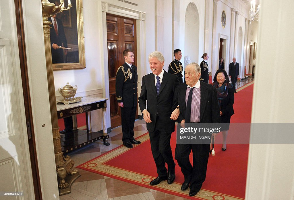 Former US president Bill Clinton (L) arrives with former Washington Post executive editor for the Presidential Medal of Freedom presentation ceremony in the East Room of the White House on November 20, 2013 in Washington, DC. The Medal of Freedom is the country's highest civilian honor. AFP PHOTO/Mandel NGAN
