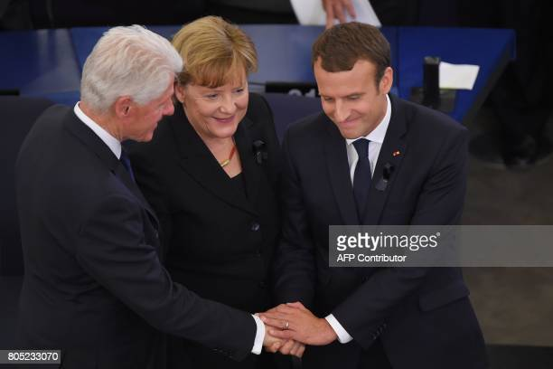 Former US president Bill Clinton German Chancellor Angela Merkel and French President Emmanuel Macron shake hands during a ceremony for late German...