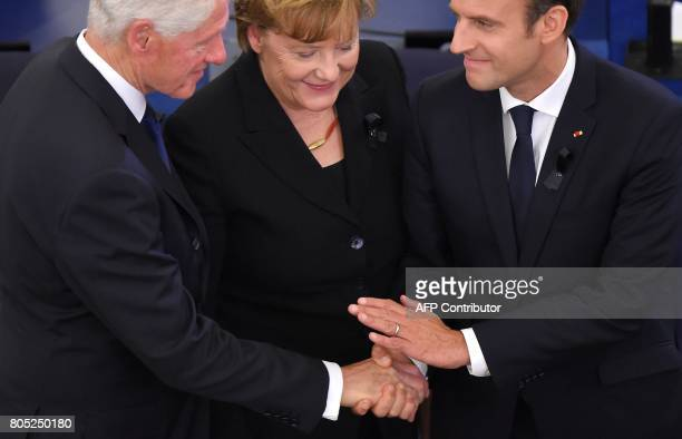 Former US president Bill Clinton Germany's Chancellor Angela Merkel and France's President Emmanuel Macron shakes hands during a ceremony for the...