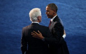 Former US President Bill Clinton greets Democratic presidential candidate US President Barack Obama on stage during day two of the Democratic...