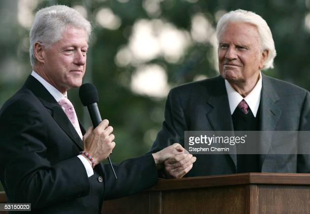 Former US President Bill Clinton holds Billy Graham's hand as he speaks during Graham's Crusade at Flushing Meadows Corona Park June 25 2005 in the...