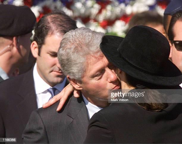 Former US President Bill Clinton hugs an unidentified women during a Memorial Service at the Pentagon October 11 2001 in Arlington VA