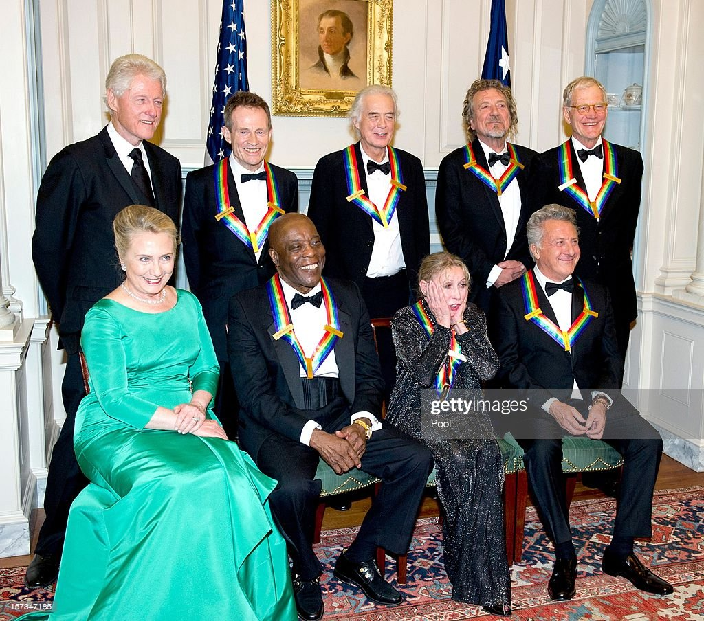Former U.S. President Bill Clinton, John Paul Jones, Jimmy Page, Robert Plant, David Letterman (L-R Front Row) U.S. Secretary of State Hillary Rodham Clinton, Buddy Guy, Natalia Makarova and Dustin Hoffman pose for a photograph following a dinner for Kennedy honorees hosted by U.S. Secretary of State Hillary Rodham Clinton at the U.S. Department of State on December 1, 2012 in Washington, DC. The 2012 honorees are Buddy Guy, actor Dustin Hoffman, late-night host David Letterman, dancer Natalia Makarova, and members of the British rock band Led Zeppelin Robert Plant, Jimmy Page, and John Paul Jones.