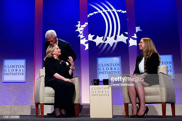 Former US President Bill Clinton kisses his wife Hillary Rodham Clinton Secretary of State as their daughter Chelsea Clinton looks on during the...