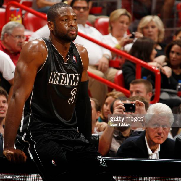Former US President Bill Clinton looks at Dwyane Wade of the Miami Heat as he stands on the sidelines during the game against the Orlando Magic on...