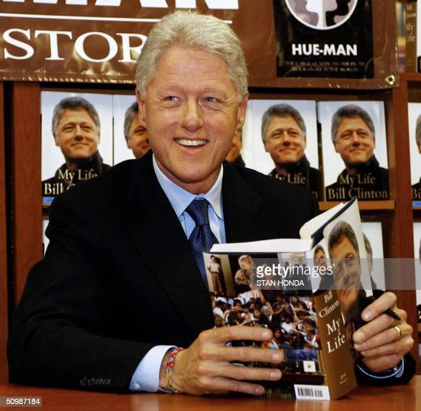 Former US president Bill Clinton poses with a copy of his new book 'My Life' during an autograph session 22 June at the HueMan bookstore in the...