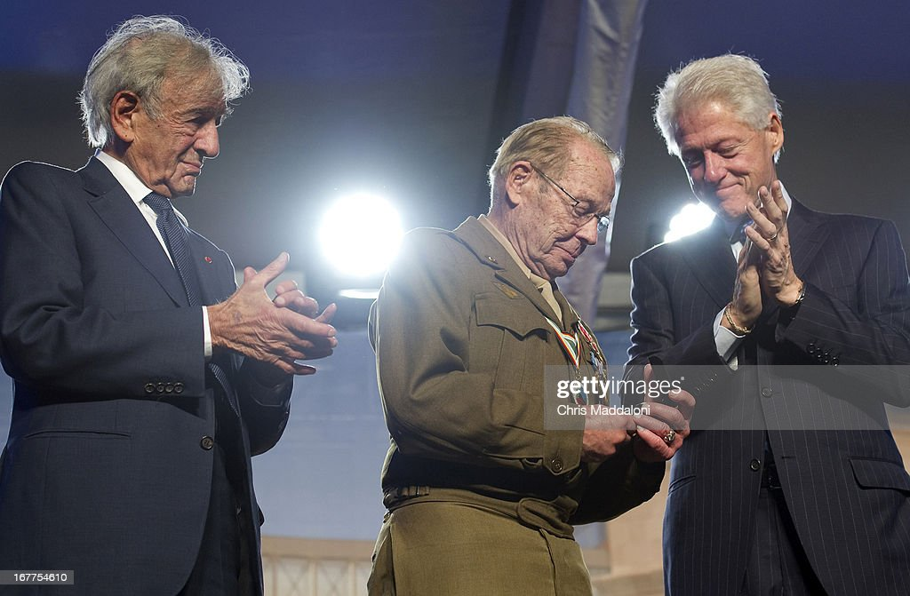 Former US President Bill Clinton presents World War II Army veteran Scottie Ooton, a member of the 84th Infantry Division which liberated Hannover-Ahlem concentration camp, the 20th anniversary pin of the United States Holocaust Memorial in Washington, D.C. on April 29, 2013. At left is Elie Wiesel, founding chairman of the Holocaust Memorial Museum.