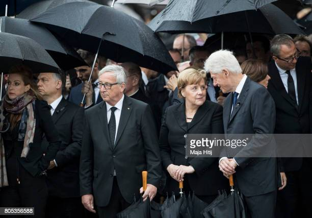 Former US President Bill Clinton President of the EU Commission JeanClaude Juncker and German Chancellor Angela Merkel pay respect to late former...