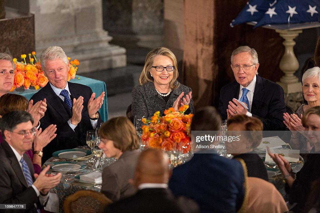 Former U.S. President Bill Clinton, Secretary of State Hillary Clinton and Senate Majority Leader Harry Reid, applaud during the Inaugural Luncheon in Statuary Hall on inauguration day at the U.S. Capitol building January 21, 2013 in Washington D.C. U.S. President Barack Obama, will be ceremonially sworn in for his second term today.