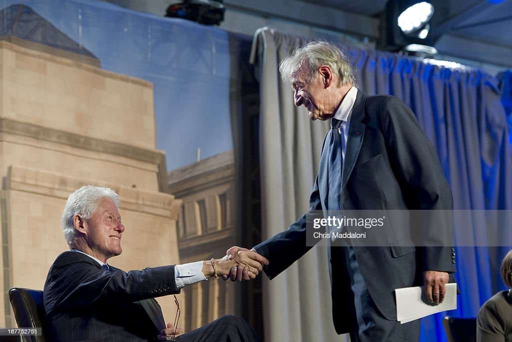 Former US President Bill Clinton shakes hands with Elie Wiesel, founding chairman of the Holocaust Memorial Museum, at a ceremony for the museum's 20th anniversary in Washington, DC.