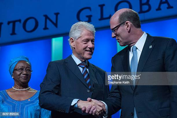 Former US President Bill Clinton shakes the hand of Sir Andrew Witty Chief Executive Office GSK while Clara Doe Mvogo Mayor of Monrovia Liberia looks...