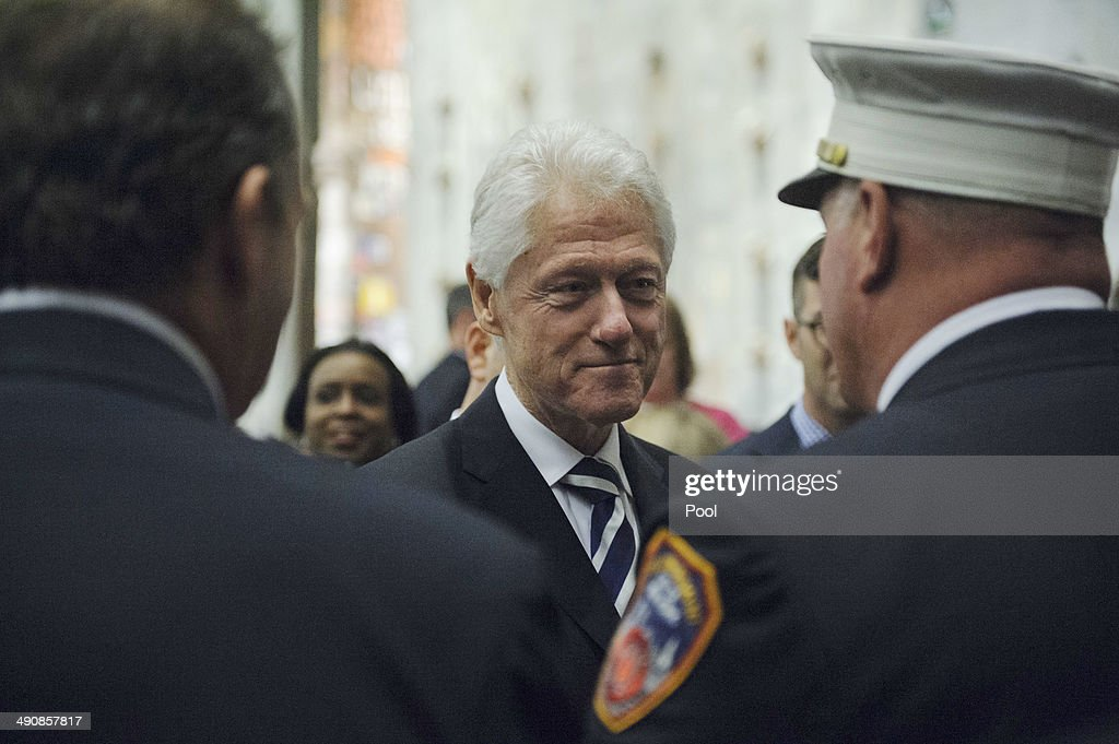 Former U.S. President Bill Clinton speaks with first responders at the end of the opening ceremony for the National September 11 Memorial Museum at ground zero May 15, 2014 in New York City. The museum spans seven stories, mostly underground, and contains artifacts from the attack on the World Trade Center Towers on September 11, 2001 that include the 80 ft high tridents, the so-called 'Ground Zero Cross,' the destroyed remains of Company 21's New York Fire Department Engine as well as smaller items such as letter that fell from a hijacked plane and posters of missing loved ones projected onto the wall of the museum. The museum will open to the public on May 21.