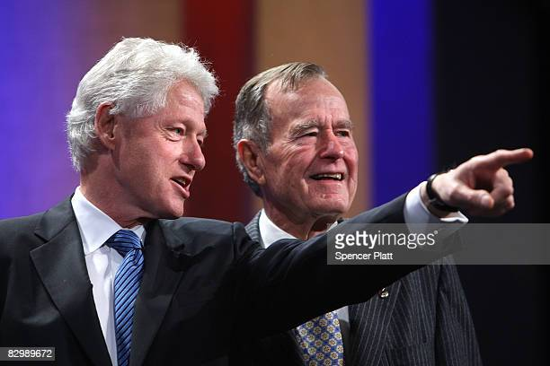 Former US President Bill Clinton stands with former US President George HW Bush during the opening session of the Clinton Global Initiative September...